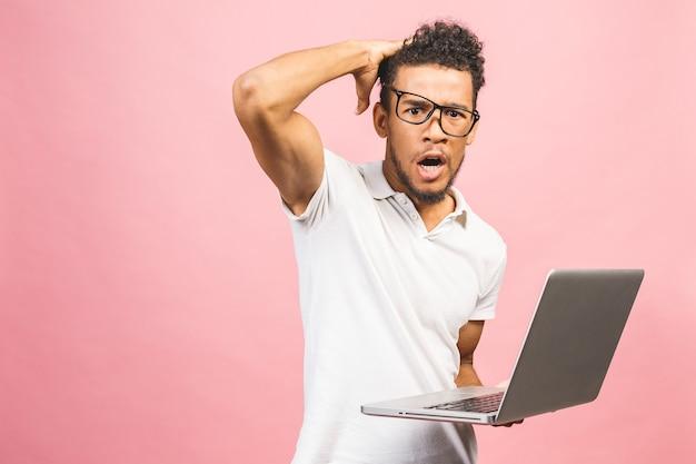 コンピューターのラップトップを使用してアフリカ系アメリカ人のビジネスマンが怒ってイライラしてイライラして叫び