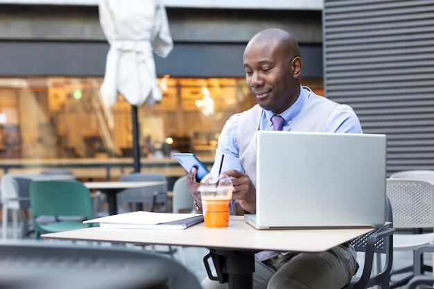 現代のコーヒーショップで働いている間彼のスマートフォンを使用しているアフリカ系アメリカ人のビジネスマン。