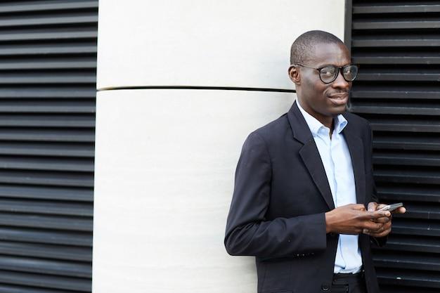 Афро-американский бизнесмен с помощью смартфона на открытом воздухе