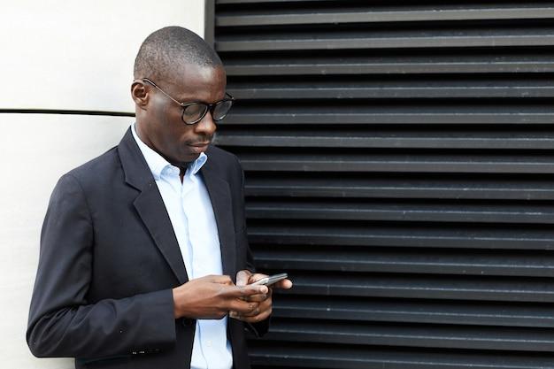 Афро-американский бизнесмен с помощью смартфона