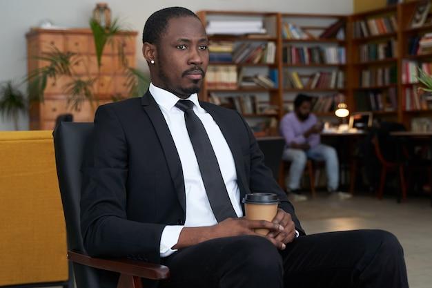 ホテルのカフェでコーヒーを飲みながらアフリカ系アメリカ人の実業家