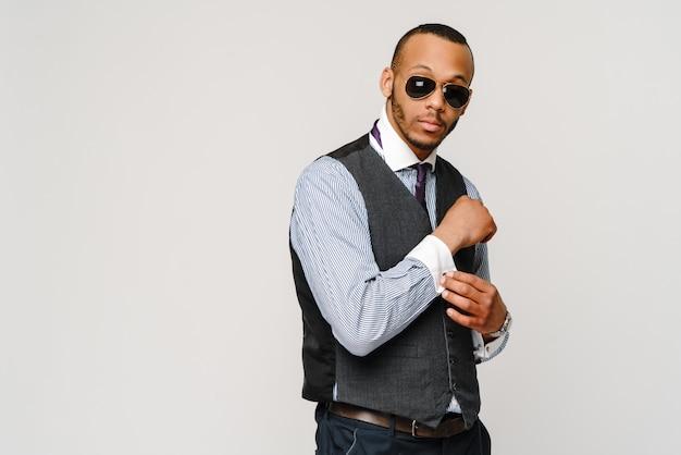 Афро-американский бизнесмен в очках портрет над серой стеной.