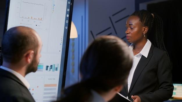 아프리카계 미국인 여성 사업가는 늦은 밤 회사 회의실에서 초과 근무를 하는 재무 전략을 브레인스토밍합니다. 다양한 다민족 팀워크 브레인스토밍 경영 프로젝트 아이디어