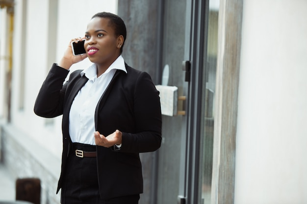 African american businesswoman in office attire smiling, looks confident and happy, busy