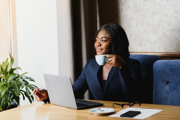 Афро-американский бизнесвумен, используя компьютер в офисе