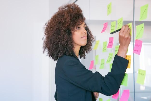 마커와 스티커에 쓰는 아프리카 계 미국인 사업가. 프로젝트에 대한 아이디어를 공유하고 메모를 작성하는 집중된 자신감 곱슬 여성 관리자