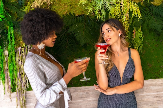 Amici femminili afro-americani e caucasici che indossano abiti fantasiosi, bere vino e parlare