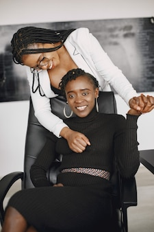 African american cheerful businesswomen at office desk in stylish suits