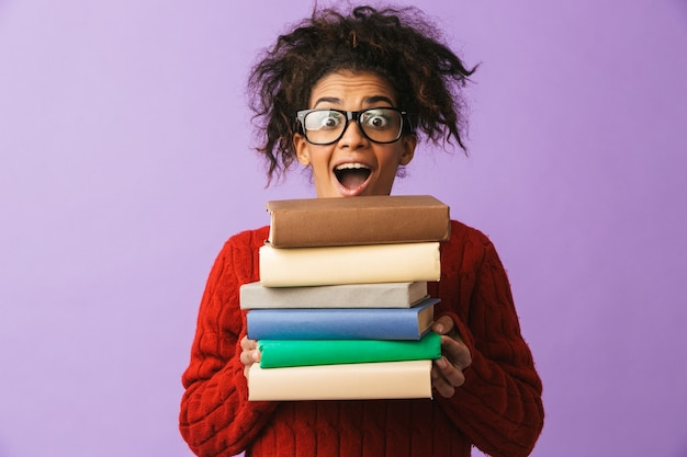 African american cheerful girl in school uniform holding bunch of books, isolated