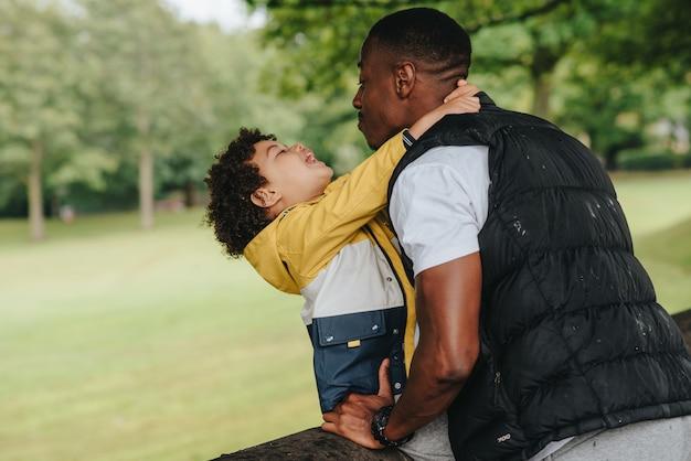 아프리카 계 미국인 아이와 그의 아버지는 공원에서 연주