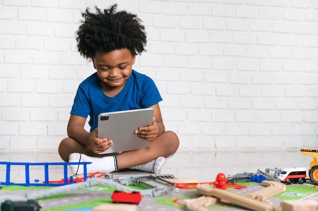 태블릿을 가지고 집에서 자신의 자동차 장난감을 가지고 노는 아프리카 계 미국인 아이