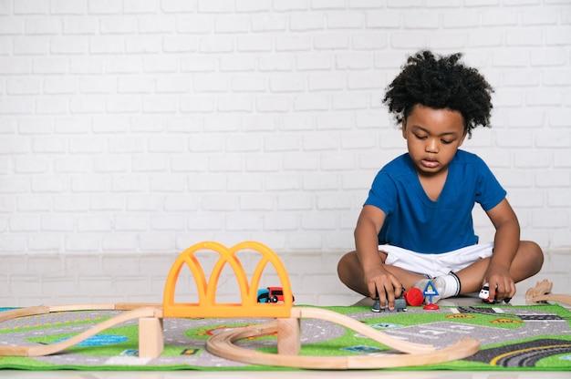 집에서 그의 자동차 장난감을 가지고 노는 아프리카 계 미국인 아이