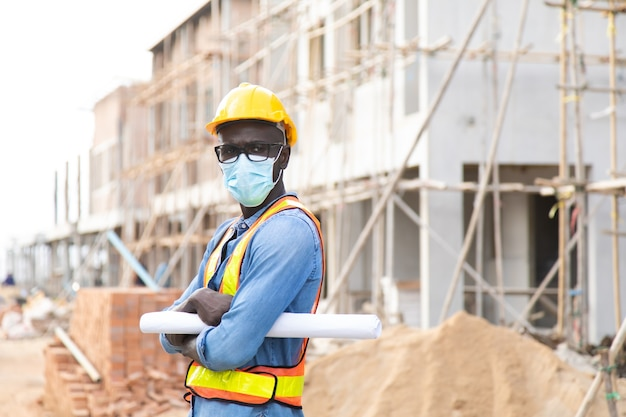 African american construction worker on building site. wearing surgical face mask during coronavirus covid and flu outbreak