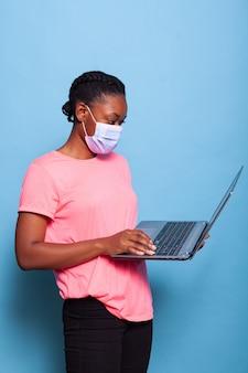 Adolescente copywriter afroamericano con maschera medica contro il coronavirus