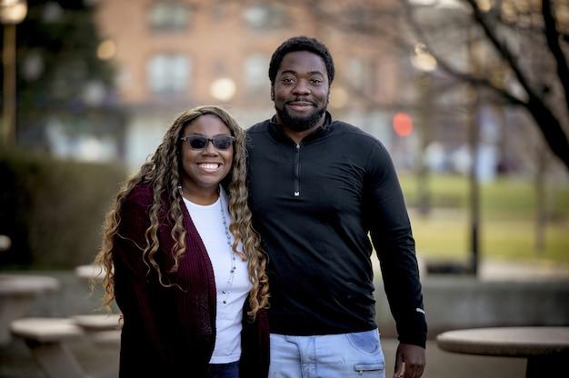 ぼやけた背景と日光の下で公園でアフリカ系アメリカ人のカップル