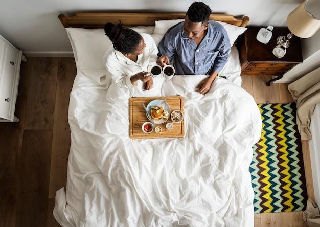 ベッドで朝食をとっているベッドでアフリカ系アメリカ人のカップル