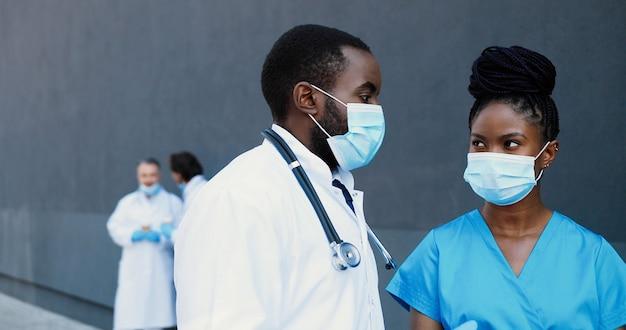 アフリカ系アメリカ人のカップル、男性と女性、仕事について話している医療マスクの医師の同僚。病院で会話をしている男性と女性の医師。コワーキング。