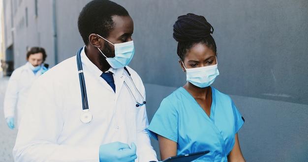 アフリカ系アメリカ人のカップル、男性と女性、医療用マスクの医師の同僚が歩いたり、話したり、タブレットデバイスを使用したりしています。男性と女性の医師がガジェットコンピューターをタップしてスクロールします。コワーキング。