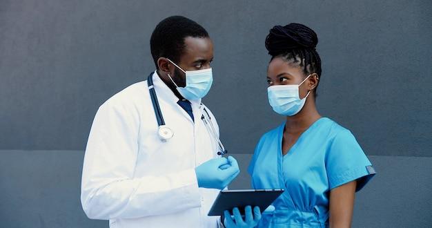 男性と女性のアフリカ系アメリカ人のカップル、タブレットデバイスを使用して作業している医療マスクの医師の同僚。男性と女性の医師がガジェットコンピュータで話し、タップし、スクロールします。