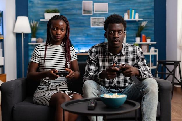 Афро-американская пара играет в видеоигры на телевизионной консоли с помощью джойстиков на телевизионном дисплее. черные женатые партнеры наслаждаются современной виртуальной игрой для развлечения и развлечения дома