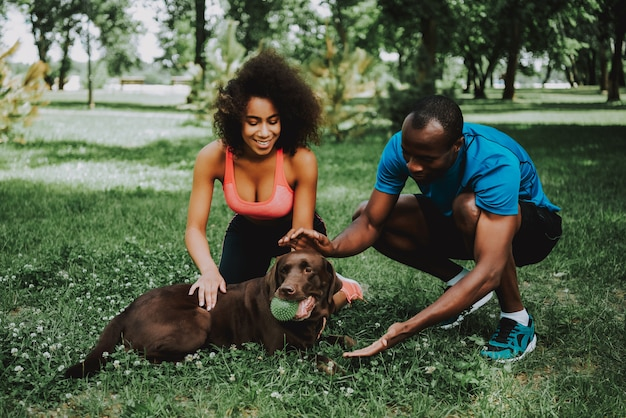 African american couple in sportswear petting dog.