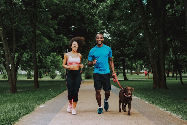 African american couple in sportswear walking dog