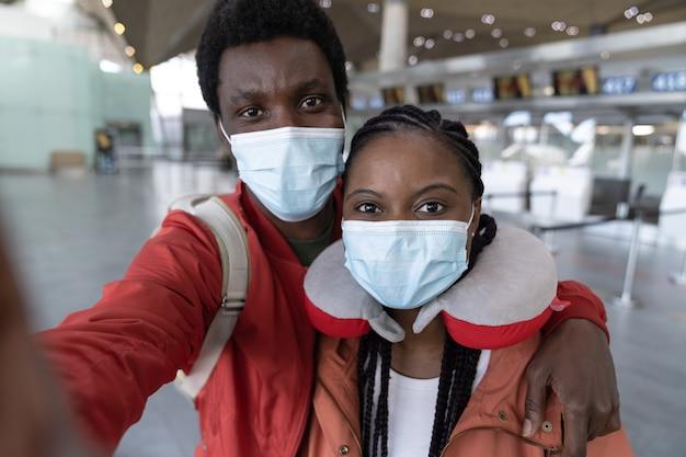 코로나 예방 접종 후 공항에서 셀카를 복용하는 아프리카 계 미국인 부부는 얼굴 마스크 여행을 착용하십시오.
