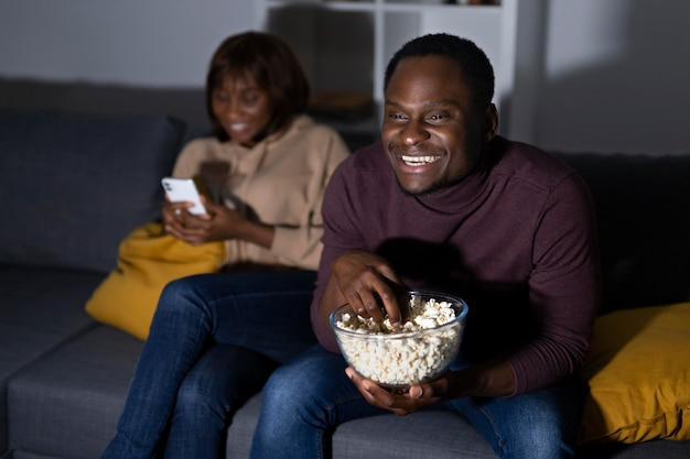 African american couple watching netflix together at home