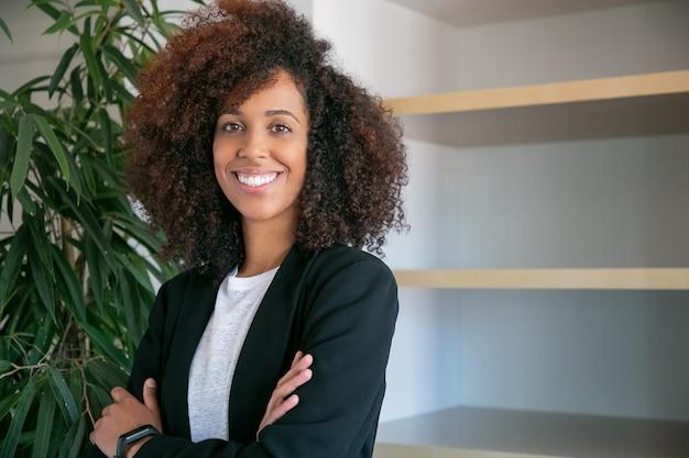 アフリカ系アメリカ人の巻き毛の実業家が手を組んで立っています。仕事でポーズのスーツで成功した自信を持って若いかなり女性会社の雇用者の肖像画。ビジネス、会社および管理の概念