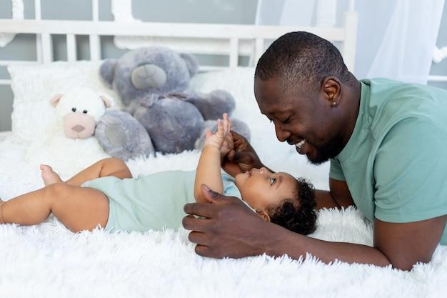 아프리카계 미국인 아빠와 아들은 집에서 침대에서 껴안고 놀고, 행복한 가족, 아버지의 날