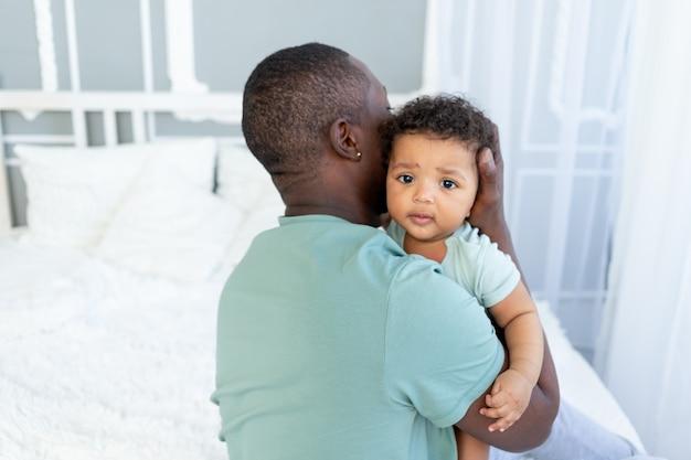아프리카계 미국인 아빠는 집에서 그를 안고 있는 아기 아들을 껴안고, 행복한 가족, 아버지의 날