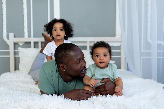 アフリカ系アメリカ人のお父さんは、寝室のベッドで家で子供の赤ちゃんと遊んで、抱きしめる、父の愛