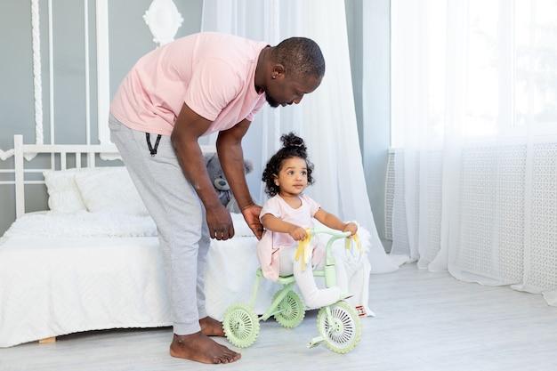 집에서 자전거를 타는 아이를 가르치는 아프리카 계 미국인 아빠 프리미엄 사진