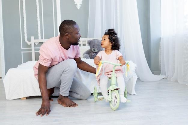 집에서 자전거를 타는 아이를 가르치는 아프리카 계 미국인 아빠