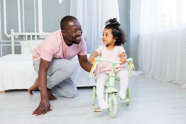 집에서 아이에게 자전거 타는 법을 가르치는 아프리카계 미국인 아빠