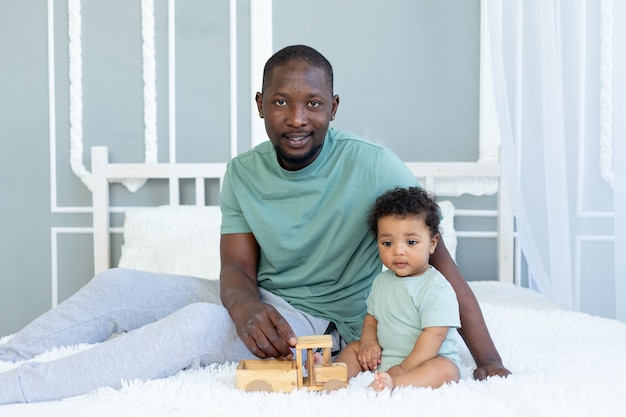 African-american dad with baby son playing on the bed at home with a wooden toy car, happy family