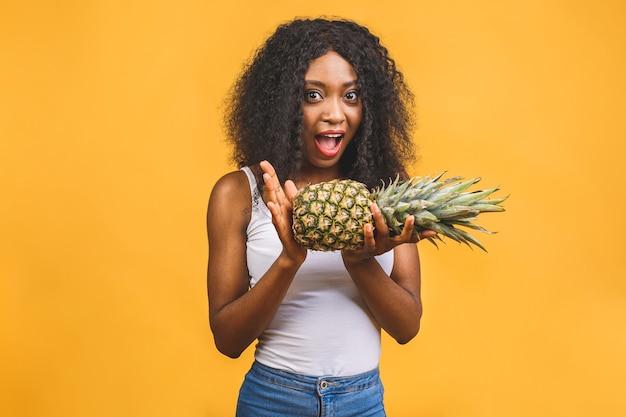 アフリカ系アメリカ人の浅黒い肌の陽気な女の子はパイナップルを手に持った