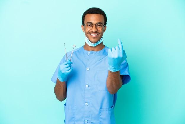 Афро-американский дантист держит инструменты на изолированном синем фоне, делая приближающийся жест
