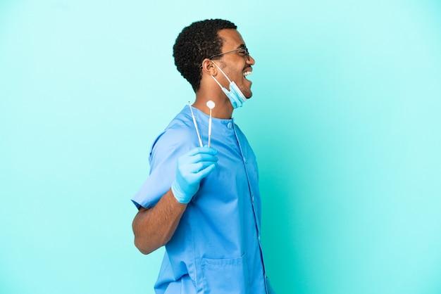 横の位置で笑っている孤立した青い背景の上にツールを保持しているアフリカ系アメリカ人の歯科医