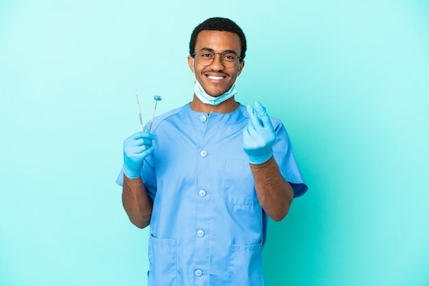 Афро-американский дантист держит инструменты на синем фоне, делая денежный жест