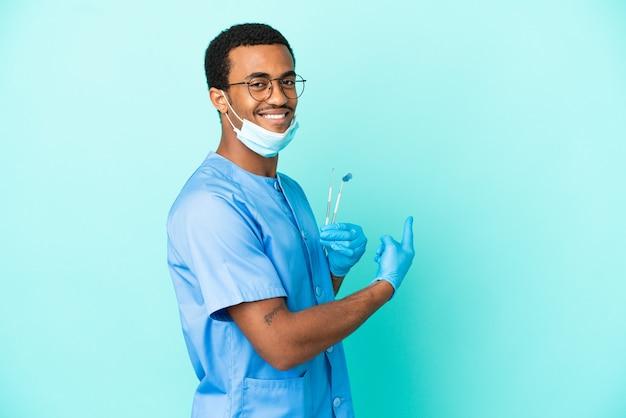 後ろ向きの孤立した青い背景の上にツールを保持しているアフリカ系アメリカ人の歯科医