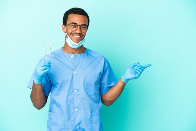 横に指を指している孤立した青い背景の上にツールを保持しているアフリカ系アメリカ人の歯科医