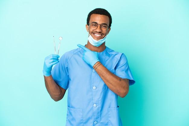 Афро-американский дантист держит инструменты на синем фоне, указывая в сторону, чтобы представить продукт