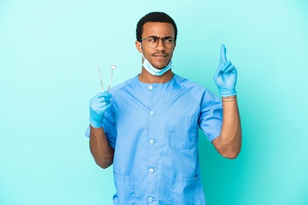 Афро-американский дантист держит инструменты на синем фоне со скрещенными пальцами и желает всего наилучшего