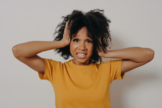 アフリカ系アメリカ人の苦しめられた若い女性は、感情のコントロールを失い、手でしっかりと耳を閉じ、私がもうそれを身振りで我慢できないことを示しました。コピースペースで白い背景の上に分離