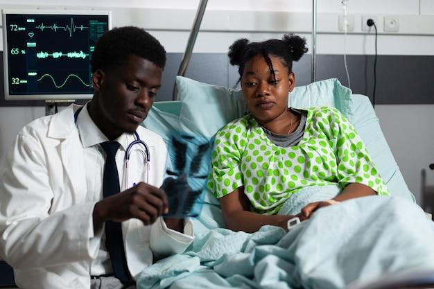 X線を見ているアフリカ系アメリカ人の医師と患者