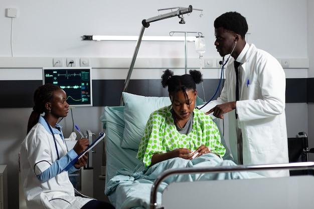 병원 병동에서 젊은 환자와 상담하는 아프리카계 미국인 의사
