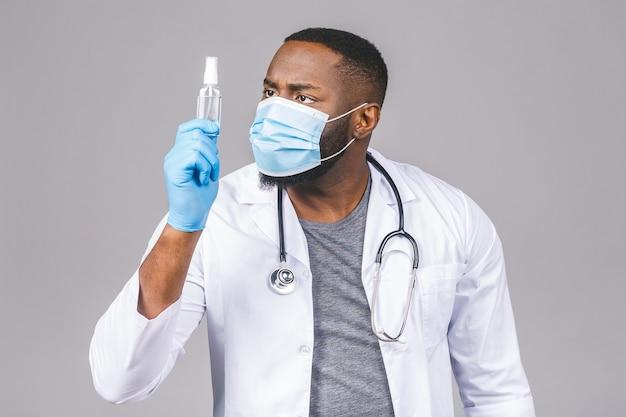 가운 얼굴 마스크 장갑에 아프리카 계 미국인 의사 남자. 병 액체 항균 소독제를 들고 있습니다.