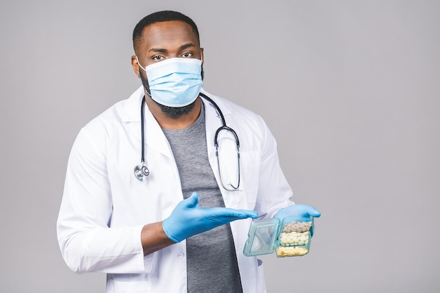 African american doctor showing pills wearing gloves. doctor holding tablets