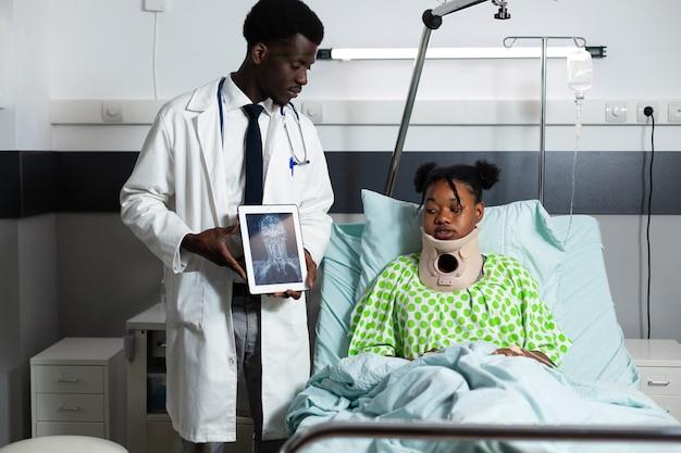 환자에게 엑스레이 태블릿을 보여주는 아프리카계 미국인 의사